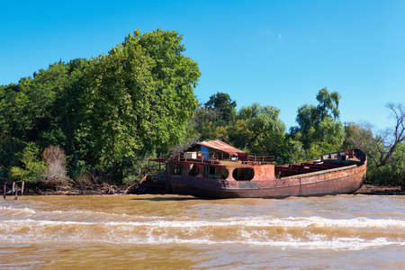 Tigra delta in Argentina, river system of the Parana Delta. Lush vegetation and old abandoned hull of rusty metal passenger or cargo ship. Lujan River delta system bringing water to Rio de la Plata.