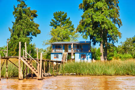 Lush vegetation, traditional wood house by wooden pier and orange clay water. Tigra delta in Argentina, river system of the Parana Delta North from capital Buenos Aires. Standard-Bild - 141629978