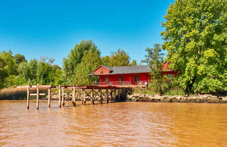 Tigra delta in Argentina, river system of the Parana Delta North from capital Buenos Aires. Lush vegetation, traditional wood house by wooden pier and orange water that carry clay to Rio de la Plata.