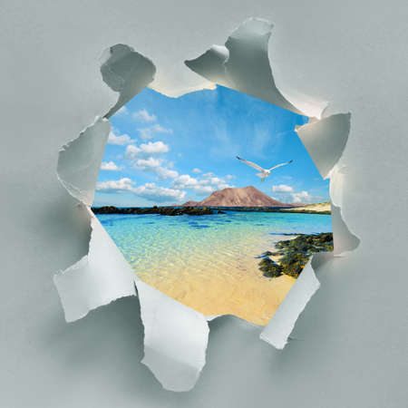 Paper hole with seashore, sandy beach in Fuerteventura, Canary islands, Spain. Free romantic seagull in the air, beautiful clouds, Lanzarote shore behind. Travel background collage.