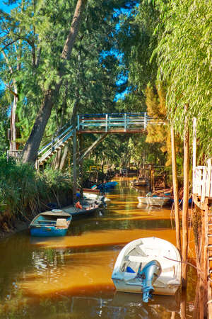 Lush vegetation, motor boats and old wooden pier. Tigra delta in Argentina, canals and river system of the Parana Delta North from capital city Buenos Aires.
