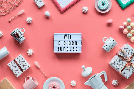 """Wir bleiben zuhause message in German, that means """"we stay at home"""" in English. Text on plastic lightboard. Trendy backgroumd, flat lay on pink background. Coffee maker, espresso cups, doughnuts. Zdjęcie Seryjne"""
