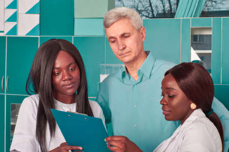 Female African medical or graduate students discuss results with Caucasian senor male group leader in research lab. Drug screening, developing antibody tests or vaccine to fight world Covid19 pandemic Stock Photo