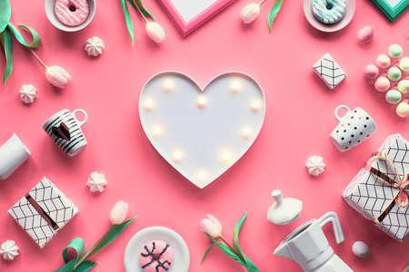 几何Spring平铺在白色和绿色的粉红色背景上。复活节,母亲节,三月八日国际妇女节。心形灯板,复活节彩蛋,咖啡杯,白色郁金香,礼物。