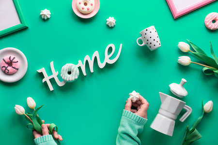 Stay home message, creative flat lay on vibrant green background with Spring objects and symbols. Hands holding white tulips and doughnut as letter O in word