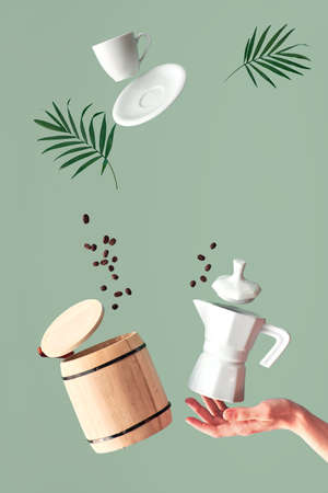Trendy levitation Flying coffee beans, espresso cup with saucer and wooden storage barrel with lid. Ceramic stove coffee maker balancing on woman's hand. Green mint modern background, palm leaves.