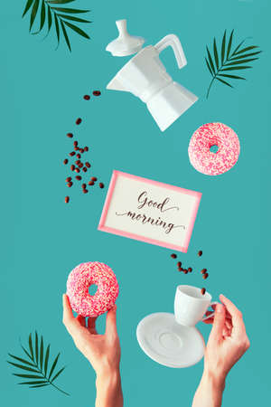 """Levitation coffee and doughnut in hands. Flying line of coffee beans. ceramic coffee maker and espresso cup held by hand. Palm leaves, frame with text """"Good morning"""". Vibrant green mint background."""