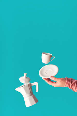 Trendy levitation Flying coffee beans, espresso cup with saucer balancing on index finger of female hand. Ceramic stove coffee maker levitation. Trendy mint blue coffee background with copy-space. Banque d'images