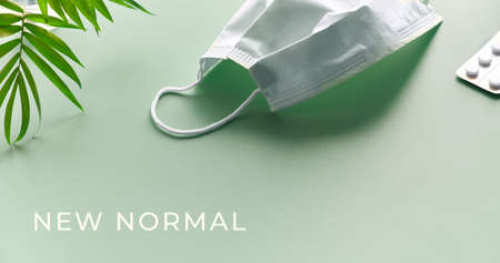 New normal. Social isolation, hygiene, prophylactic measures to fight novel coronavirus. Mint green background with face mask, pills and natural palm tree leaf