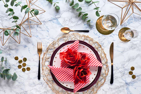 Christmas table setting with red stripy napkin and silk amaryllis flowers. golden utensils and fresh eucalyptus leaves on white marble background. Flat lay, top view on decorated tablе