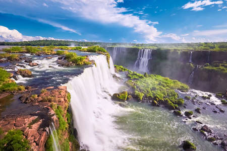 Iguazu waterfalls in Argentina, view from Devil's Mouth. Panoramic view of many majestic powerful water cascades with mist. Side view of the wide powerful waterfall. Bird view of the ravine.