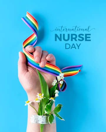 International nurse day concept. Hand of mature woman with chamomile flower bouquet attached with medical aid patch holding rainbow ribbon. Creative modern flat lay, top view on blue background.