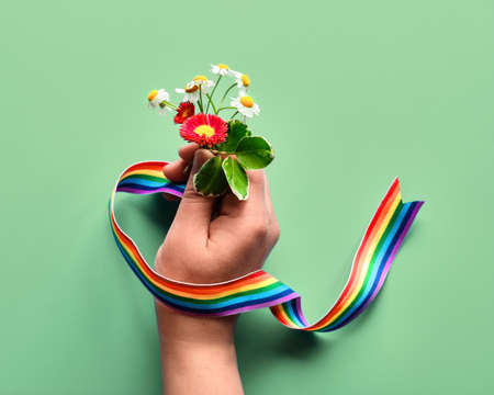Thank you doctors and nurses! Rainbow text, ribbon in hand of woman with chamomile and primrose flowers, simple bouquet. Creative flat lay, top view on light green mint background.