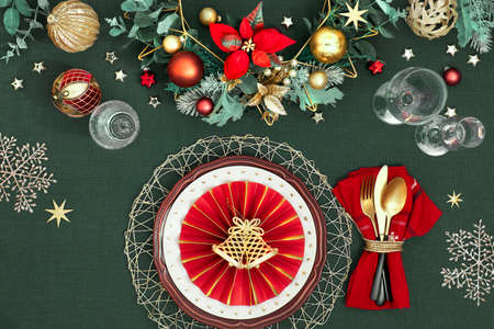 Christmas table setup with dark red white plates, red paper ring and poinsettia, golden utensils. Red, green and golden gilded decorations. Flat lay on dark green linen textile background.