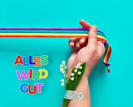 "Text ""Alles wird gut"" in German means ""Everything will be well"" in English. Hand hold rainbow ribbon."