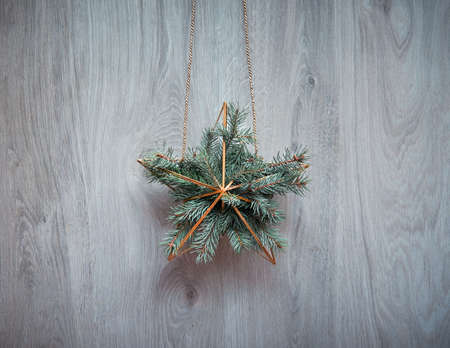 Christmas wreath in a shape of golden geometric star with fir twigs hanging on rustic wooden door. Traditional Xmas ornament. Minimalist zero waste modern elegant Xmas decor.