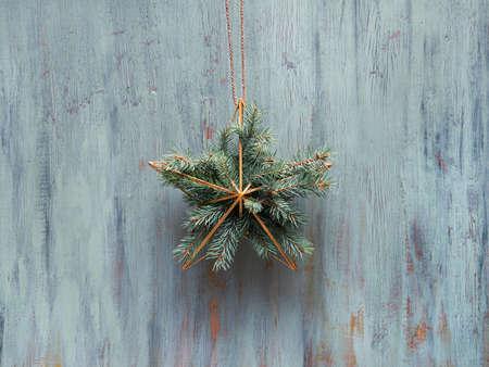 Christmas wreath in a shape of golden geometric star with fir twigs hang on rustic wooden door, traditional Xmas ornament. Minimalist zero waste trendy Xmas decor. 版權商用圖片