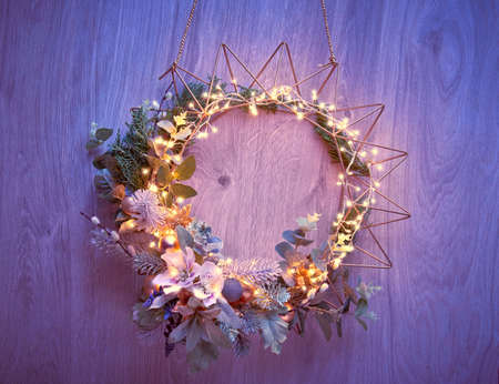 Decorative Christmas wreath with fir, winter leaves and flowers on geometric golden metal frame with light garland hanging on a door. 版權商用圖片