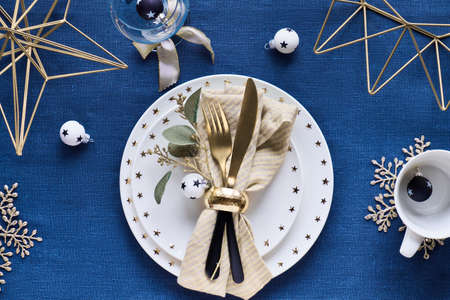 Christmas table setup with white plate, golden utensils and gilded geometric metal decor and gilded snowflakes. Flat lay on dark blue linen textile table cloth background. White balls with black stars 版權商用圖片