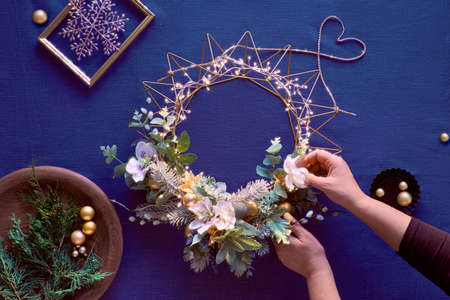 Making of decorative Christmas wreath on classic blue linen. Female hands make handmade wreath. Golden Xmas trinkets, anemone flowers, winter plants and lights on metal base. Flat lay, top view. 版權商用圖片