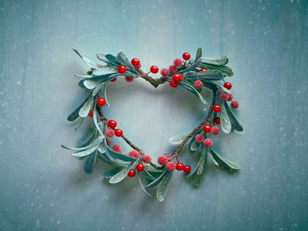 Decorative Christmas heart shaped wreath with frosted mistletoe leaves and red berries hanging on a light textured door. Toned Xmas decoration background in green and red. 版權商用圖片 - 148090472