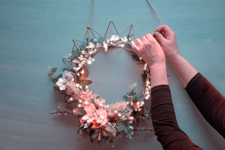 Making Christmas wreath, creative flat lay, top view on purple background with female hands, handmade wreath on metal base, Xmas decorations and evergreens.