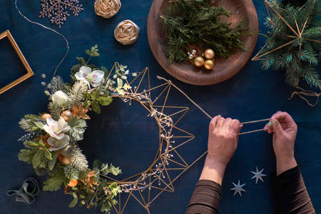 Making of decorative Christmas wreath on classic blue linen. Woman hands with handmade wreath. Xmas decorations, golden trinkets, decorative anemone flowers, winter plants on metal base, top view. 版權商用圖片