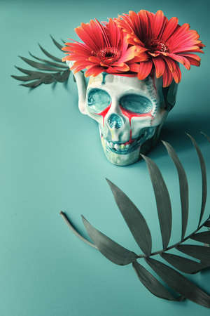 skull with coral color gerbera flowers and palm leaves on tile green background. Creative concept. Surreal feel, eery spooky atmosphere.
