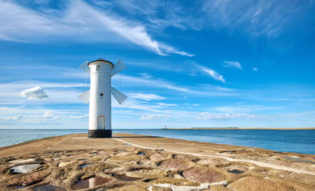Panoramic image of seawall and retro windmill lighthouse in Swinoujscie, a port in Poland on the Baltic Sea.