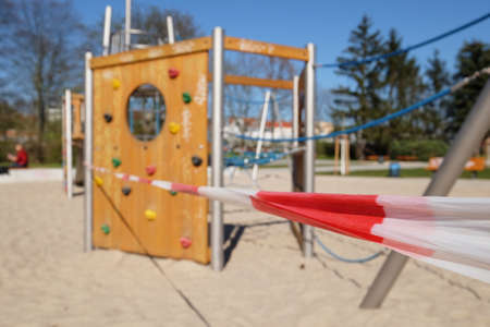 Empty playground without kids, closed to children and parents. Cut off with striped red white warning tape. Forbidden to entry by authorities. Restrictions, quarantine for novel Coronavirus Covid-19.