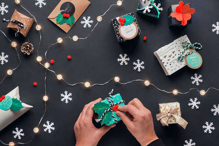 Merry Christmas and a Happy New Year! Presents wrapped in gift boxes with tags. Hands decorating box with holly. Flat lay, top view. Light garland, green alarm, snowflakes on black paper background.