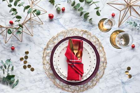 Christmas table setting with red napkin, golden utensils and fresh eucalyptus leaves on white marble background. Flat lay, top view on table with golden cutlery, white plates and geometric hexagons.