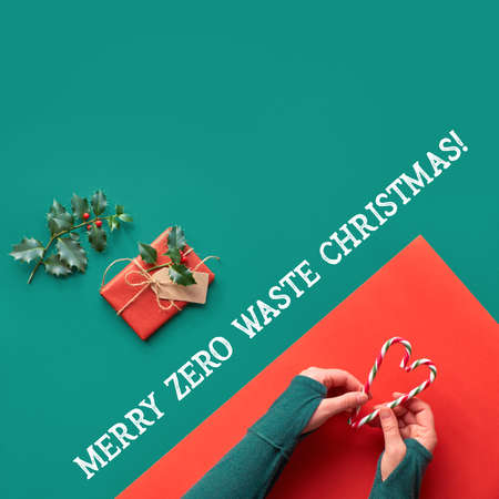 Creative diagonal geometric flat lay on green and red paper with long shadows of leaves. Hands hold stripy candy canes heart shape. Merry zero waste Christmas, eco friendly concept square composition.