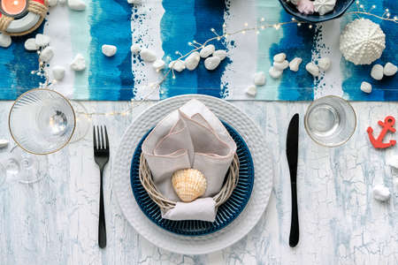 Contemporary summertime table setting with nautical sea decorations on blue and white stripy runner, classic blue white plates, utensils on white rustic table. Top view, casual modern lunch.
