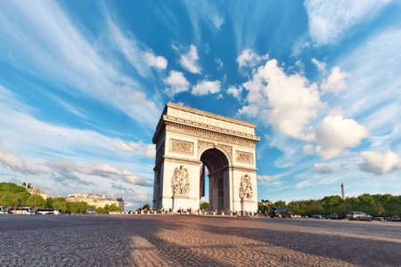 Arc de Triumph in Paris, France, on an empty square with feather clouds in blue sky above, panoramic image.