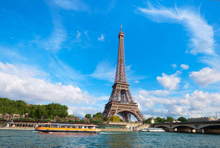 Cityscape of Paris with the Eiffel tower on a sunny day. Tourist boats on river Seine. Bright sunny day with feather clouds in blue sky. 写真素材