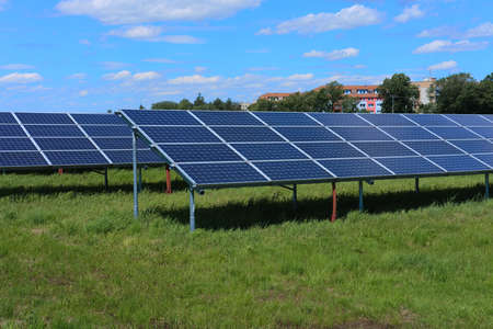 Solar power plant, blue solar panels on a field with fresh green grass under blue sky with clouds Фото со стока