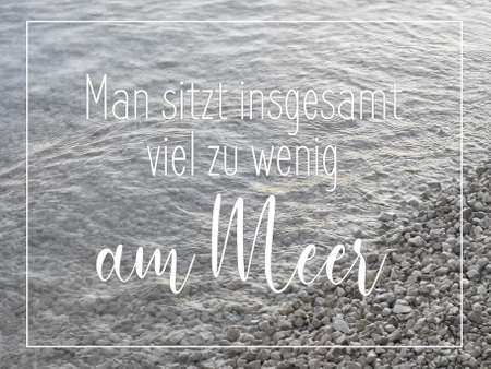 """Pebble stones by the sea, diagonal water edge. Warm grey natural background. Text here is in German, it means """"one sits far too little by the sea"""". Reklamní fotografie"""