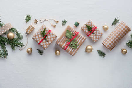 DIY Christmas gifts and handmade decorations. Natural plastic free eco-friendly Xmas celebration. Gift boxes in craft wrapping paper, geometric arrangement with fir twigs, toys on white textile.
