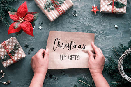 DIY Chritstmas gifts and handmade decorations. Natural plastic free eco-friendly Xmas celebration. Copy-space, text Christmas DIY gifts on craft wrapping paper in hands Flat lay, grey background.