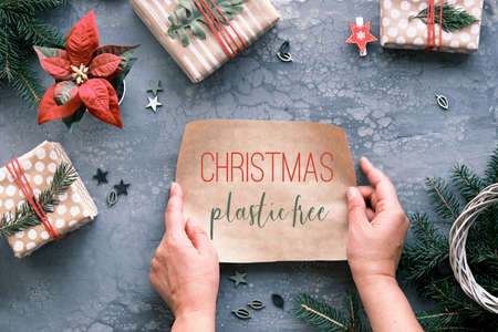 Text Christmas plastic free on piece craft wrapping paper in hands. Flat lay on grey table with Xmas gifts wrapped in handmade brown paper