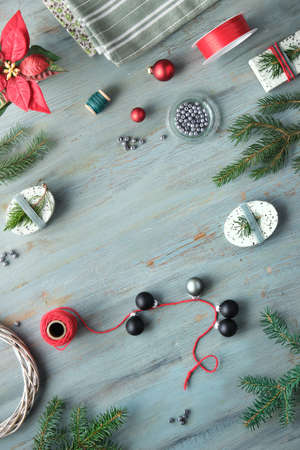 Christmas flat lay in grey, green, white and red, text space. Xmas background with gift boxes and handmade decorations