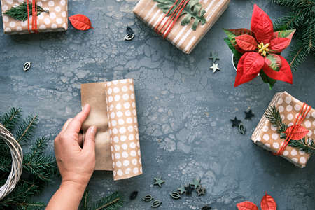 DIY Christmas gifts and handmade decorations. Natural plastic free eco-friendly Xmas celebration. Craft wrapping paper in hands. Flat lay, top view on grey background.