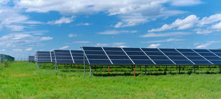 Solar power plant, blue solar panels on grass field under blue sky with clouds. Solar power generation, renewable energy production