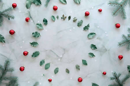 Christmas flat lay on green and red. Marble stone background, copy-space. Xmas background with natural fir twigs, holly leaves and glass trinkets.