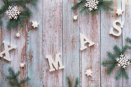Creative Christmas flat lay with white letters Xmas on wooden boards. Rustic design, fir twigs decorated with wooden snowflakes and white star trinkets. Imagens