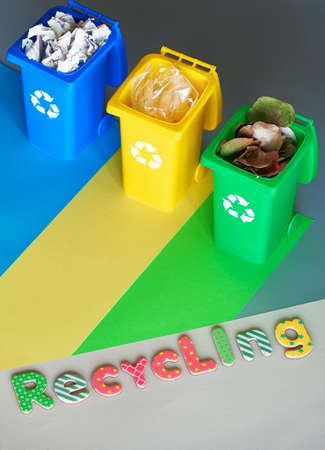 Three color coded recycling plastic bins, isometric projection, copy-space. Recycling sign on the bins, blue, yellow, green. Waste separation to reduce anthropogenic impact on environment.