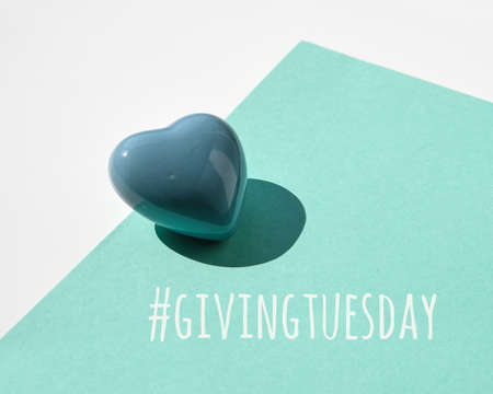 Giving Tuesday, global day of charitable giving. Black Friday of Charity, global charity campaign. Ceramic heart on white and mint green paper background. Text hashtag givingtuesday.
