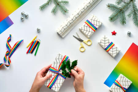 Hands decorating Christmas gift boxes with rainbow ribbon, LGBT flag symbol.