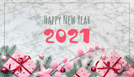 Text Happy New Year 2021. Panoramic flat lay on white marble background. Decorative border with wrapped gift boxes and winter decor.